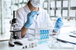 biochemistry-laboratory-research-scientist-or-medical-in-lab-coat-holding-test-tube-with-using